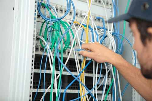 telecom technician plugging in ethernet cables cable management